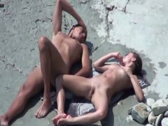 Young nudists having sex on the rocks