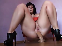 Bimbo slides a large sex toy deep inside of her anus