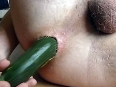 Green zucchini up his asshole in close up