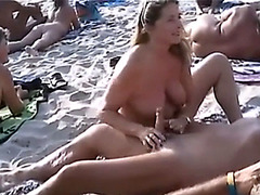 Naughty girls playing with dicks at the nudist beach