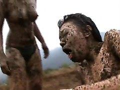 Two Asian girls wrestling on manure field