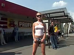 Naughty blonde girl shows her breasts and upskirt pussy outdoors