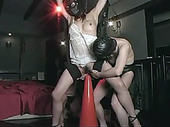 Masked girl sits her pussy on a traffic cone