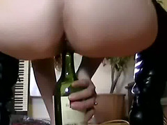 Slut in sexy leather boots rides a wine bottle