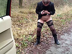 Mature in overcoat and boots pisses on a dirt rode