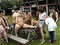 Outdoor mature orgy in the grass