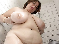Fat chick in the shower rubs her huge tits