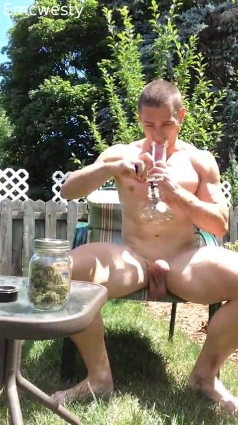 Naked young man takes bong rips outside