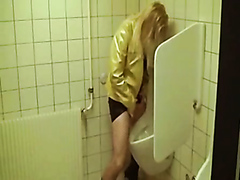 Drunk blonde pees in a urinal