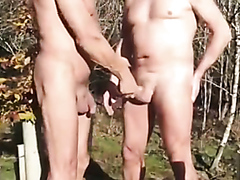 Mature guys stroking each other's cocks outdoors