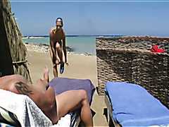 Busty slut masturbates and sucks a dick on the beach