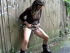 Curly brunette unloads a huge pee near public park