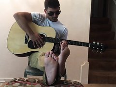 quiet jock hunk playing guitar barefoot
