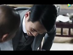 (humiliation scene) a man in a suit is  forced clean boots