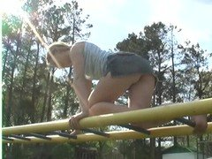 Pony tailed bitch plays at monkey bars