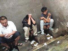 A row of chinese men with exposed cocks in traditional squat toilet