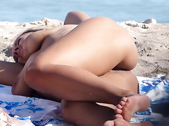 Sexy babe rolling around on the beach naked