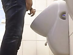 Young man pissing, spying nice cock from stall