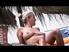 Busty milf tanning at the beach
